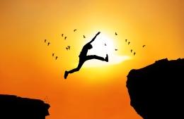 Silhouette of man jumping a wide cliff. Shot outdoor at sunrise